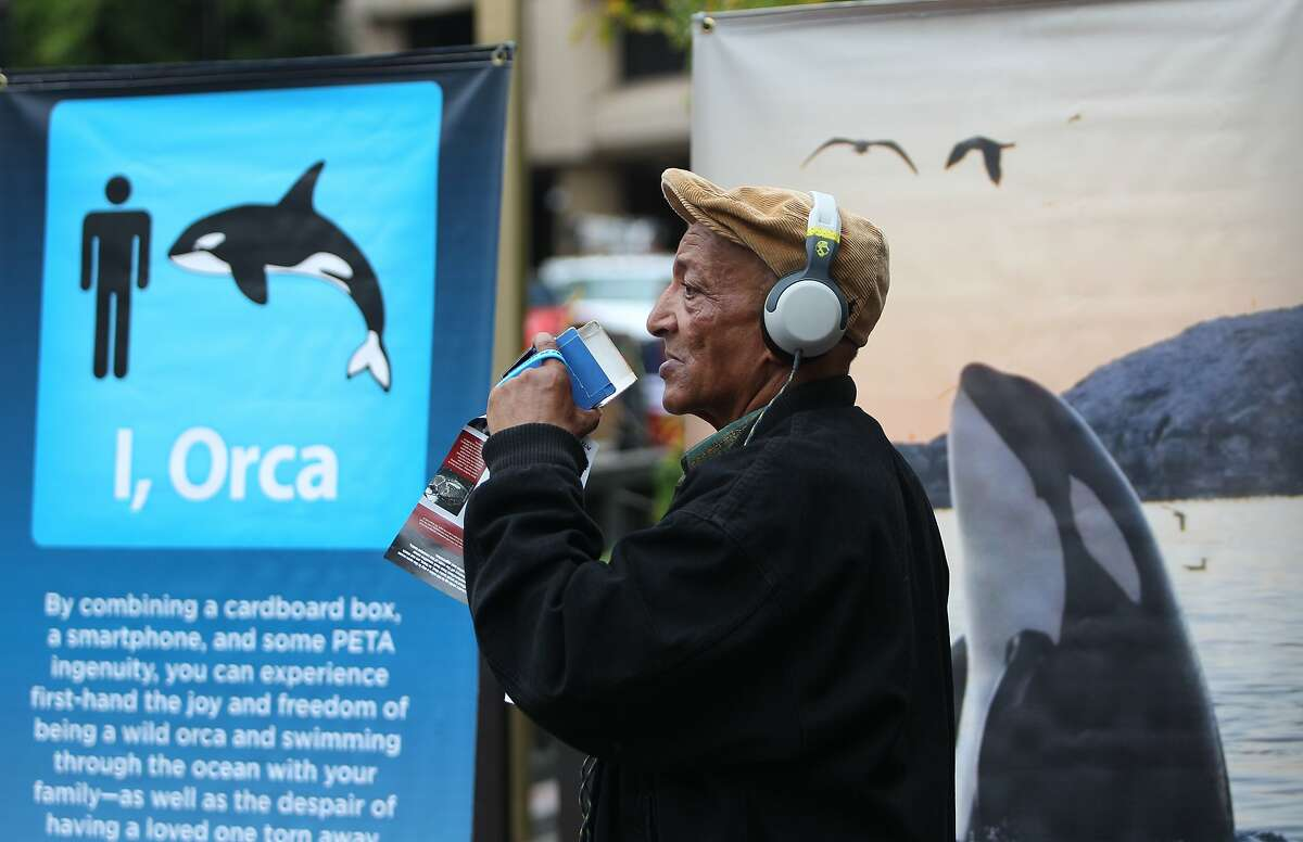 Benyam Bekele stops at a PETA booth at Market and 5th Streets in San Francisco, California, to try out the