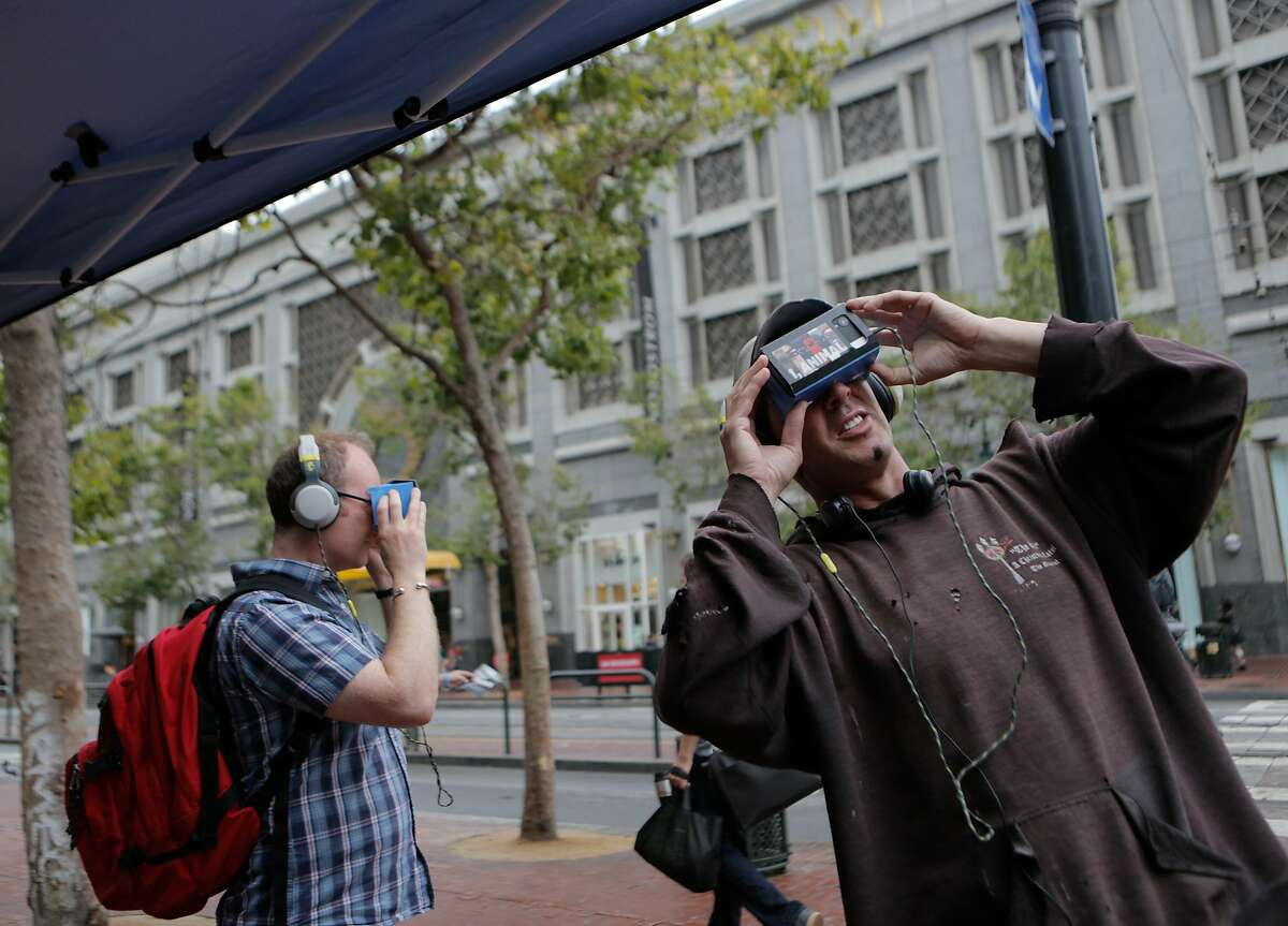 Steven Pantell (right) and Mark Robson stop at a People for the Ethical Treatment of Animals (PETA) booth at Market and 5th Streets in San Francisco, California, to try out the