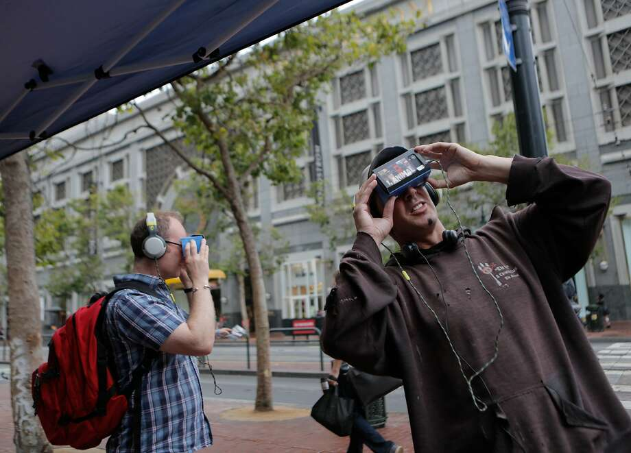 """Steven Pantell (right) and Mark Robson stop at a People for the Ethical Treatment of Animals (PETA) booth at Market and 5th Streets in San Francisco, California, to try out the """"I, Orca"""" virtual experience on Wednesday, June 10, 2015. By using wireless virtual reality goggles, viewers are able to """"swim with the orcas"""" and meet a mother orca whose baby was captured and sent to SeaWorld. PETA is strongly opposed to SeaWorld because the theme park keeps orcas in captivity. Photo: Loren Elliott, The Chronicle"""