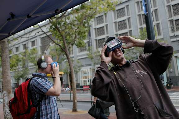 "Steven Pantell (right) and Mark Robson stop at a People for the Ethical Treatment of Animals (PETA) booth at Market and 5th Streets in San Francisco, California, to try out the ""I, Orca"" virtual experience on Wednesday, June 10, 2015. By using wireless virtual reality goggles, viewers are able to ""swim with the orcas"" and meet a mother orca whose baby was captured and sent to SeaWorld. PETA is strongly opposed to SeaWorld because the theme park keeps orcas in captivity."