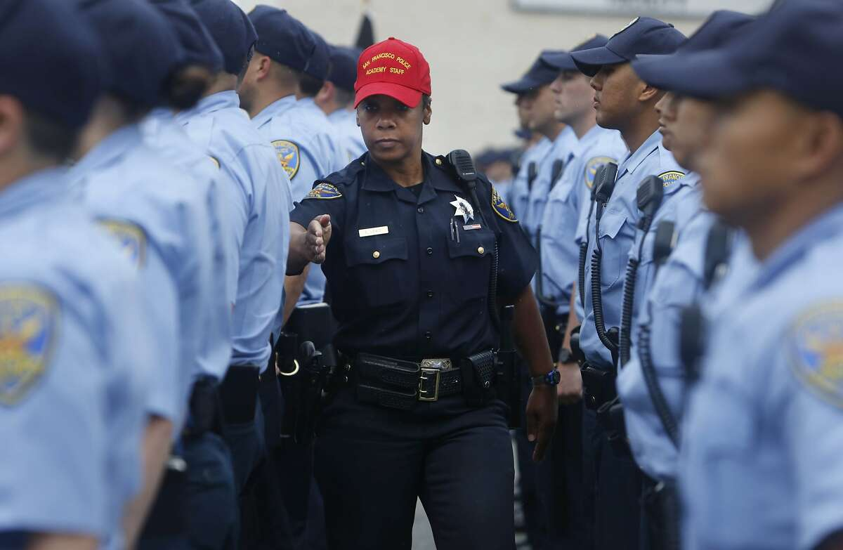 Recruit training officer Edie Lewis (center) checks the formation of recruits and their uniforms as they stand in formation during an exercise at the San Francisco Police Academy Regional Training Center on Wednesday, June 10, 2015 in San Francisco, Calif.