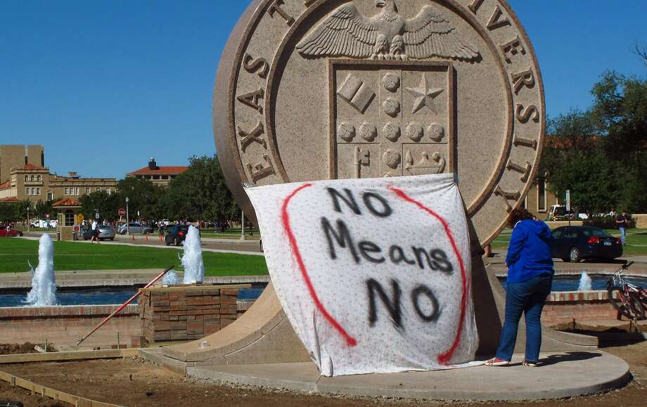 "A Texas Tech student helps drape a sign over the university's seal at the Lubbock campus in 2014 during a protest against the school's ""rape culture."" Photo: Betsy Blaney, Associated Press"