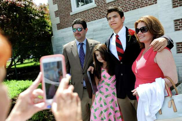 "Graduate Eugene ""E.R."" Spada, 18, center, poses for pictures with his father E.R. Spada, left, sister Emily Spada, 11, and mother Kim Spada, right, after commencement exercises on Tuesday, June 9, 2015, at The Albany Academy in Albany, N.Y. (Cindy Schultz / Times Union) Photo: Cindy Schultz / 00032210A"