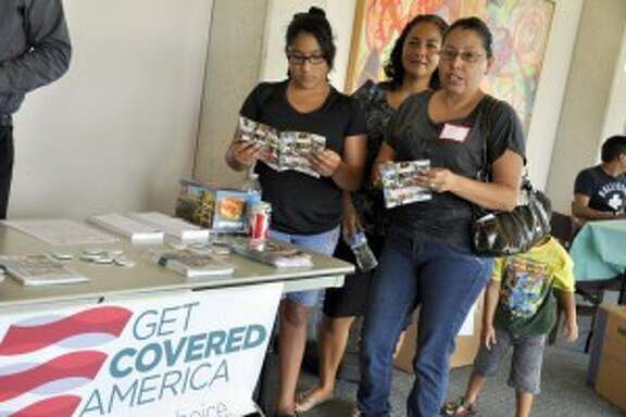 A family reviews Affordable Care Act insurance marketplace information at a health fair at the University of Houston during the 2014 enrollment. period.