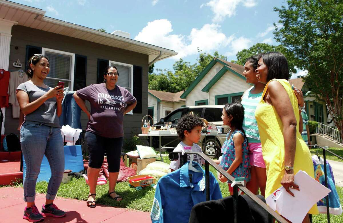 """While block walking Saturday June, 6, 2015 Mayor Ivy Taylor poses for a photo with Jaden Fernandez, 4, (from left), Aaliyah Fernandez, 5 and Aricela Flores, 10 as Griselle Fernandez and Elaine Flores take photos during a yard sale they were having at their aunt's house on Bailey Avenue. Fernandez and Flores said they had to look several times as the mayor was approaching the house to make sure it was her. After walking Taylor continued on with campaigning at a meet and greet at the Alamo Beer Company. Mayor Taylor has been having between 6-8 events a day that she has been attending or participating in either officially or campaigning. While Taylor says that it can be very busy, it is only for a certain time period before the election is done, and she is calm about the election and is ready for outcome either way. """"The election is not tied to my identity,"""" said Taylor."""