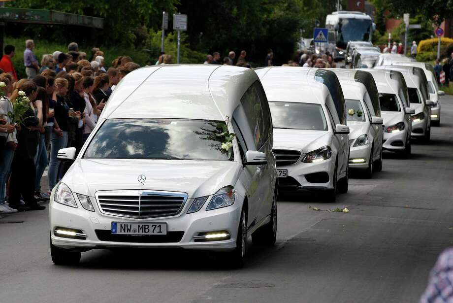 White hearses carrying the remains of high-school students killed in the Germanwings plane crash in France approach the students' high school in Haltern, Germany. The first burials will be on Friday. Photo: Michael Probst /Associated Press / AP