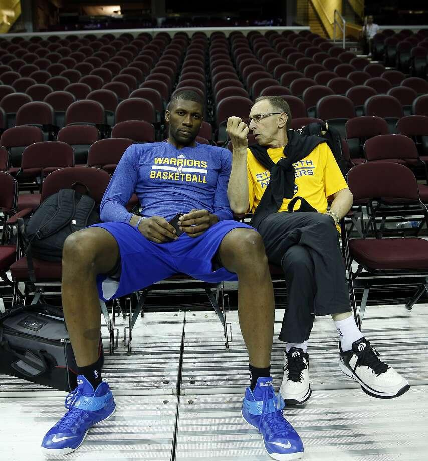 Ron Adams (right) talks with Festus Ezeli. Photo: Scott Strazzante, The Chronicle