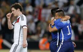 Germany's Sebastian Rudy, left, touches his nose as United States' Bobby Woods celebrates after scoring his side's second goal during the soccer friendly match between Germany and the United States in Cologne, western Germany, Wednesday, June 10, 2015. (AP Photo/Frank Augstein)