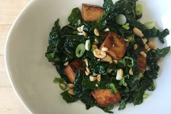 Warm tofu and kale salad with peanuts and green onions.