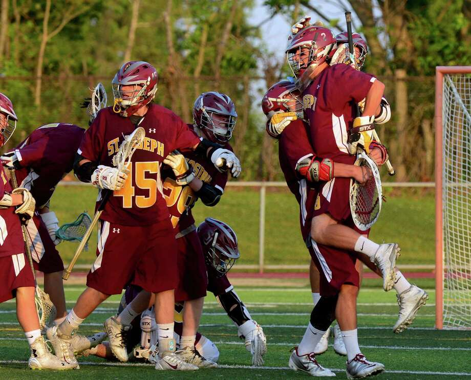 St. Joseph team members rush to goalie Mike Braddick, at right, to celebrate their defeat of East Catholic, during Class S lacrosse semifinals action in West Haven, Conn., on Wednesday June 10, 2015. Photo: Christian Abraham, Christian Abraham/Hearst Connect / Connecticut Post