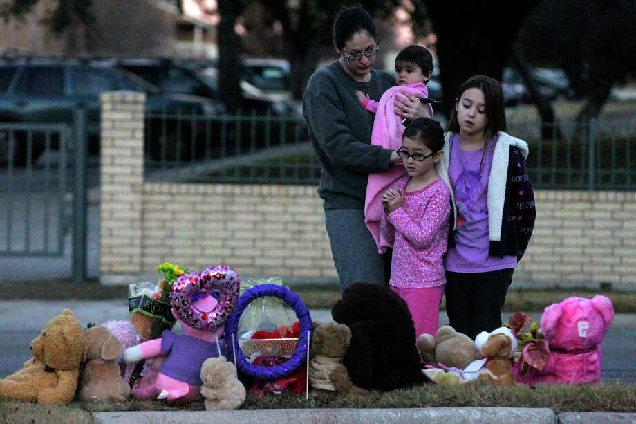Monica Bloompott — with children Kyra, 10 months (from left); Meya, 5; and Kayla, 9 — visits on Jan. 16, 2014, the area where Tatyana Babineaux, 9, was hit by a truck the previous day in the 11700 block of Braesview. Tatyana was walking to Larkspur Elementary at about 7 a.m. when she was struck by a hit-and-run driver. Photo: John Davenport /San Antonio Express-News / ©San Antonio Express-News/Photo may be sold to the public