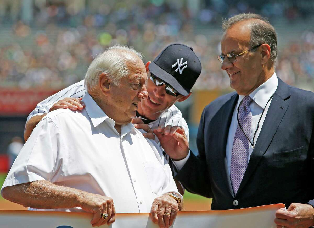 New York Yankees manager Joe Girardi, center, greets Hall of Fame manager Tommy Lasorda, left, as former Yankees manager and Hall of Fame manager Joe Torre, looks on before the start of a baseball game at Yankee Stadium in 2015. Lasorda died of a heart attack Thursday night, MLB said. (AP Photo/Kathy Willens)