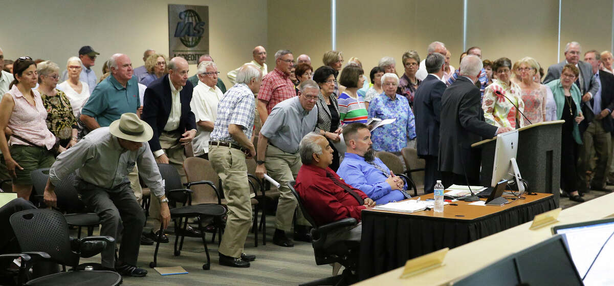 Most of the audience rises as Charles Gorham asks those in opposition to stand as residents of the Oakwell Farms neighborhood appear before the Planning Commission to express their objections to a proposed apartment dwelling development within their area on June 10, 2015.
