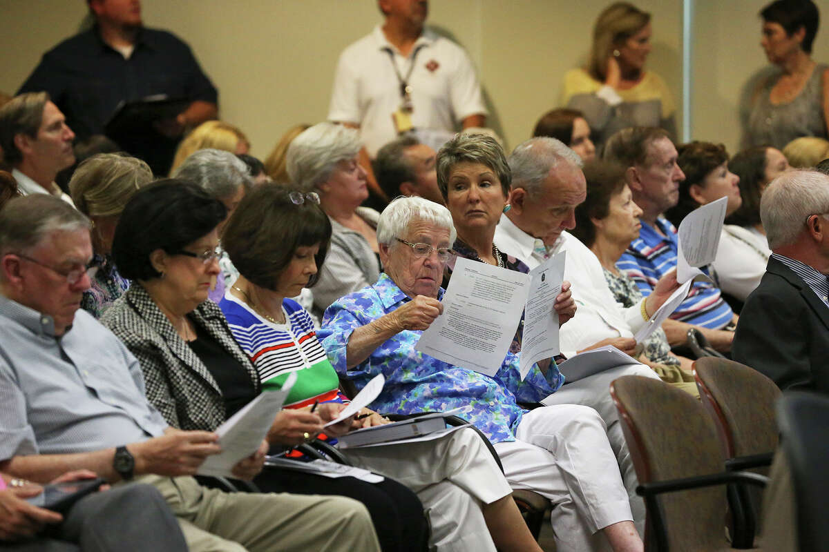 Tina Weir (center) reads fact sheets as she and other residents of the Oakwell Farms neighborhood appear before the Planning Commission to express their objections to a proposed apartment dwelling development within their area on June 10, 2015.