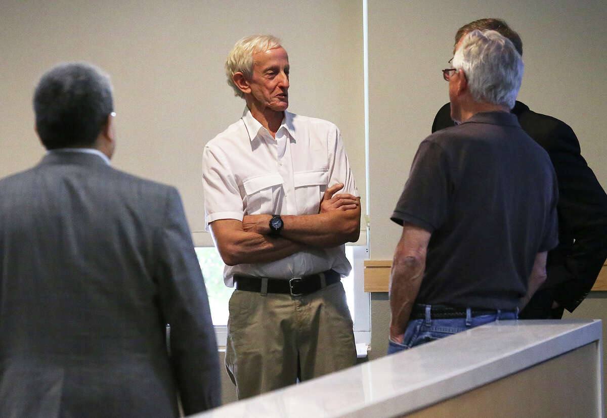 Laddie Denton, an original co-builder with Robert Tobin, chats as residents of the Oakwell Farms neighborhood appear before the Planning Commission to express their objections to a proposed apartment dwelling development within their area on June 10, 2015.