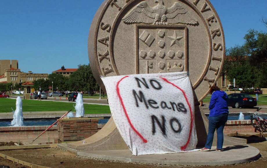 "FILE - In this Wednesday, Oct. 1, 2014 file photo, Texas Tech freshman Regan Elder helps drape a bed sheet with the message ""No Means No"" over the university's seal at the Lubbock, Texas campus to protest what students say is a ""rape culture"" on campus. A picture of a banner at a Sept. 20 Phi Delta Theta fraternity gathering, briefly posted online, read, ""No Means Yes,"" followed by a graphic sexual remark. A study by the Canadian Institutes of Health Research and the University of Windsor published on Wednesday, June 10, 2015 found that a program that taught college women ways to prevent sexual assault cut in half the chances they would be raped over the next year. It was the first large, scientific test of resistance training, and the strong results should spur more universities to offer it, experts say. (AP Photo/Betsy Blaney) ORG XMIT: RPBB501 Photo: Betsy Blaney / AP"