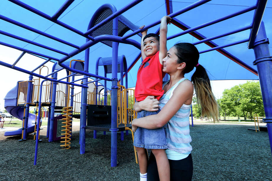 Alyssa helps her brother reach a bar overhead. Besides the massive shade canopy, other park improvements include new fitness equipment, a resurfaced soccer field and trail upgrades. Photo: Marvin Pfeiffer /San Antonio Express-News / Express-News 2015
