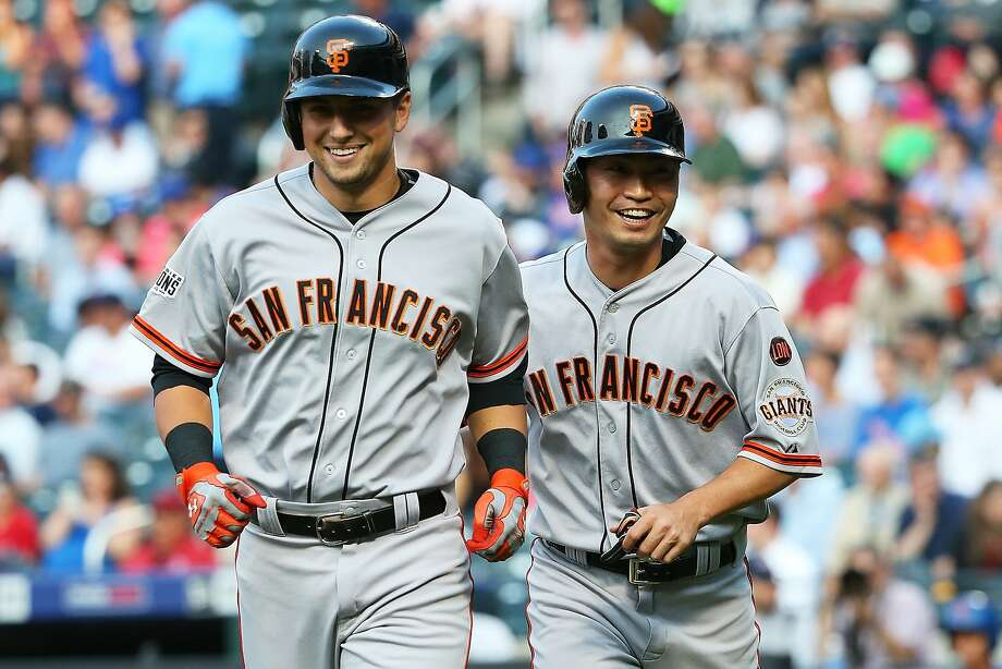 Joe Panik (left) heads to the dugout along with Nori Aoki (right) after both scored on Panik's two-run homer in the first inning off Mets ace Matt Harvey. Photo: Mike Stobe, Getty Images
