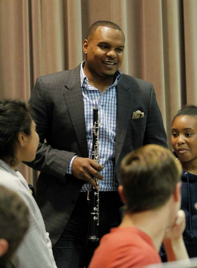"Chester Pitts, co-founder of the Chester Pitts Charitable Foundation holds an oboe as he chats with M.C. Williams Middle School band and orchestra students whom they brought to observe rehearsal at Immanuel and Helen Olshan Texas Music Festival at the University of Houston Moores School of Music on Wednesday, June 10, 2015, in Houston. The Chester Pitts Charitable Foundation's mission is to evoke artistic interest in our community's children through programs designed to inspire natural creativity, arouse enthusiasm for knowledge, and energize the spirit of our youth. ""Music was my game changer growing up, the discipline it taught me has helped me be successful. So it is important that I instill this beautiful art form into my children and the children in the community."" Photo: Karen Warren, Houston Chronicle / © 2015 Houston Chronicle"