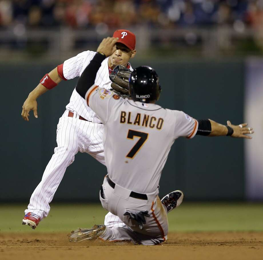 Gregor Blanco, who is sidelined by a concussion, tries to steal unsuccessfully as Phillies shortstop Cesar Hernandez prepares to tag him out on Friday. Photo: Matt Slocum, Associated Press