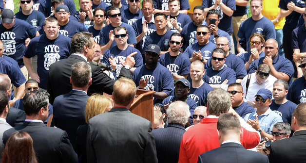 Governor Andrew Cuomo, at podium, pointing, speaks to New York City firefighters and police officers as they rally to demand additional disability protections at the Capitol Wednesday June 10, 2015 in Albany, NY.  (John Carl D'Annibale / Times Union) Photo: John Carl D'Annibale, Albany Times Union / 10032241A