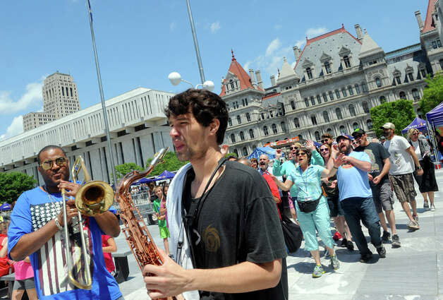 Glen David Andrews, left, and his band lead a New Orleans style second line parade through the Empire State Plaza during their Made in the Shade of the Egg lunchtime show on Wednesday June 10, 2015 in Albany , N.Y.  (Michael P. Farrell/Times Union) Photo: Michael P. Farrell, Albany Times Union