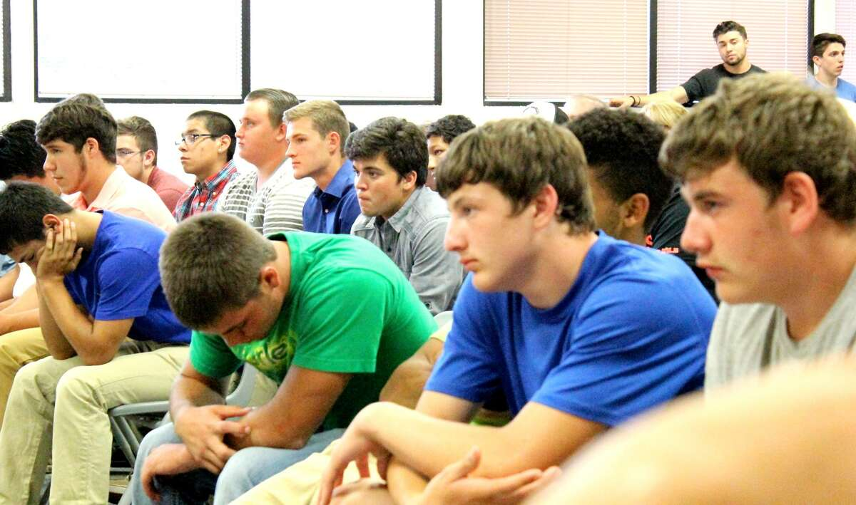 Members of the Mineral Wells High School football team listen as a teammate addresses the Mineral Wells ISD school board as part of their protest over what they call unfair treatment of quarterback hopeful Trent Guinn (second row, blue shirt) by head coach Gerald Perry. (Photo courtesy Mineral Wells Index)