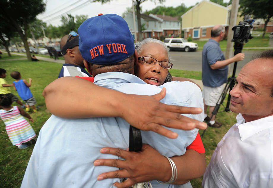 Trumbull Gardens resident Karen Bracey hugs Bruce Nelson, both of Bridgeport, outside the affordable housing complex on Reservoir Avenue in Bridgeport, Conn. where nine people were shot and one killed on Thursday, June 11, 2015. Former Bridgeport mayor and current mayoral candidate Joseph Ganim is at right. Photo: Brian A. Pounds / Hearst Connecticut Media / Connecticut Post