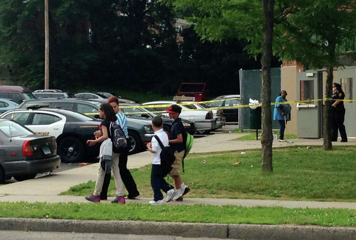 Students are walked to a bus stop, past the scene of an overnight shooting in Bridgeport, Conn. on Thursday June 11, 2015. Nine people, six adult males and three adult females, were shot when gunfire erupted at the troubled Trumbull Gardens public housing complex in Bridgeport's North End shortly after 1 a.m. Thursday.