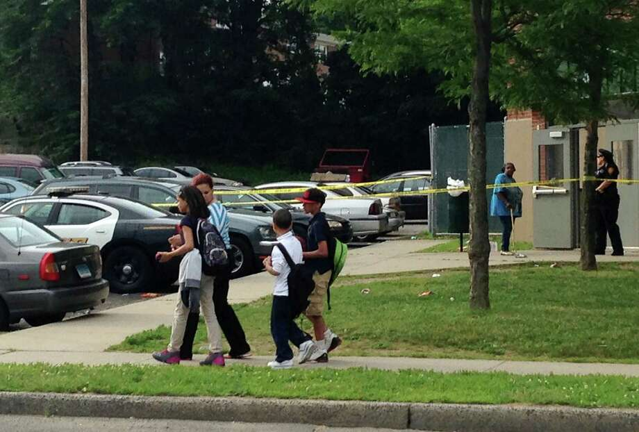 Students are walked to a bus stop, past the scene of an overnight shooting in Bridgeport, Conn. on Thursday June 11, 2015. Nine people, six adult males and three adult females, were shot when gunfire erupted at the troubled Trumbull Gardens public housing complex in Bridgeport's North End shortly after 1 a.m. Thursday. Photo: Frank Juliano / Hearst Connecticut Media / Connecticut Post