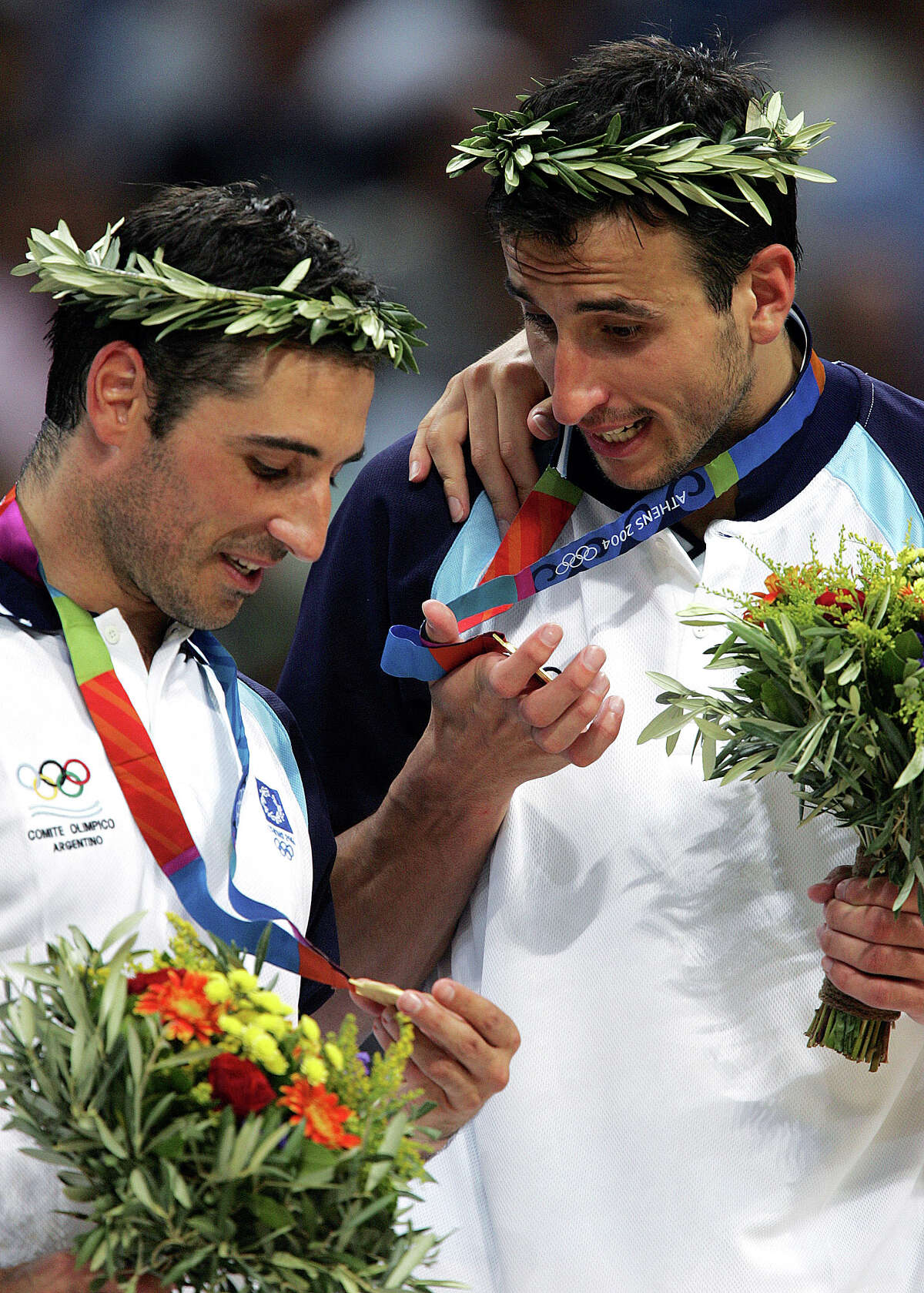 Argentina's Alejandro Montecchia, left, and Emanuel Ginobili study their gold medals after beating Italy 84-69 in their game at the Olympic Indoor Hall during the 2004 Olympics in Athens, Greece on Saturday, Aug. 28, 2004. (AP Photo/Dusan Vranic)