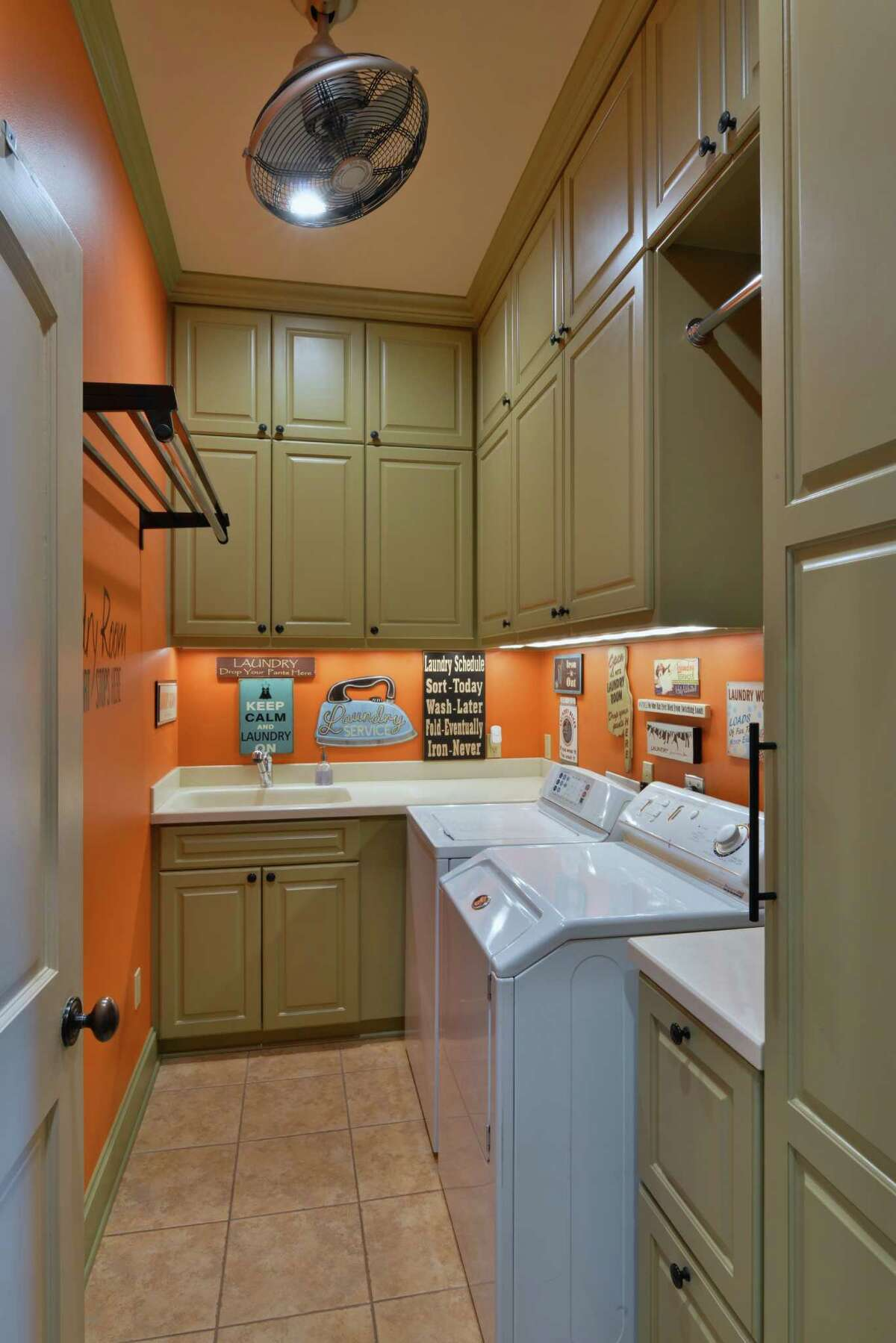 In this Nottingham Forest home in far West Houston, designer Chandra Stone carved out space on the first floor for a long, narrow utility room with plenty of storage. She installed two hanging bars and filled the room with drawers and cabinets.