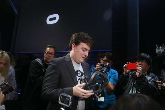 "Palmer Luckey, Oculus founder,  holds the Oculus Rift while putting in on after an Oculus VR news conference ""Step into the Rift' at Dogpatch Studios on Thursday, June 11, 2015 in San Francisco, Calif."