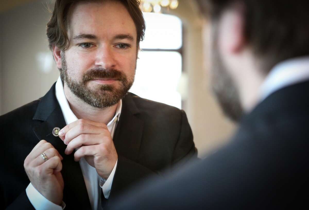 Matthew Baier, COO of Built.io, puts on his sommelier pin at home before he goes into work on June 10, 2015 in San Francisco, Calif.
