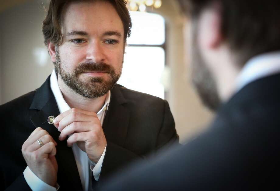 Matthew Baier, COO of Built.io, puts on his sommelier pin at home before he goes into work on June 10, 2015 in San Francisco, Calif. Photo: Amy Osborne, Special To The Chronicle