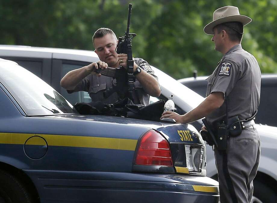 New York State Police prepare their equipment during a search for two escaped prisoners near Dannemora, N.Y., Thursday, June 11, 2015. Police have blocked off the main road outside a northern New York village as authorities concentrate their sixth day of searching for David Sweat and Richard Matt on a swampy area just a couple miles from the prison the convicts broke out of last weekend. (AP Photo/Seth Wenig) Photo: Seth Wenig, Associated Press