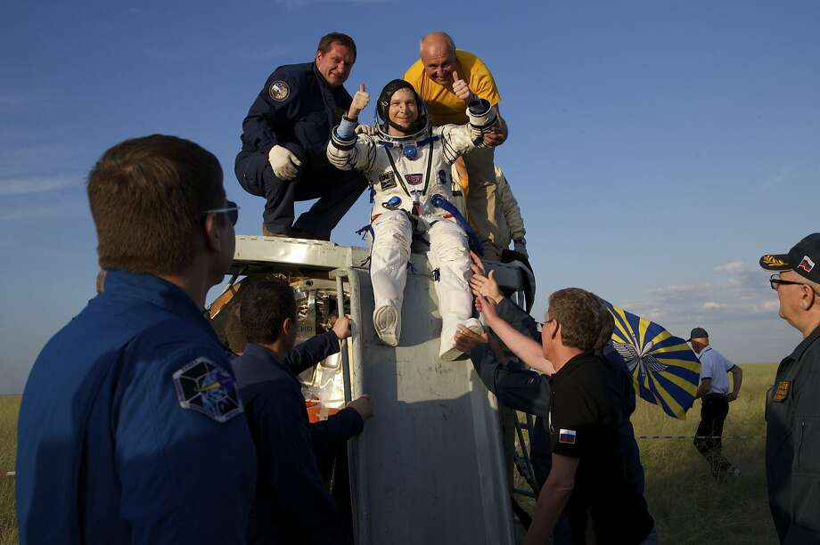 American Terry Virts gives a thumbs up as he is helped out of a Soyuz space capsule after he and two other astronauts landed in Kazakhstan. Photo: Ivan Sekretarev, Associated Press