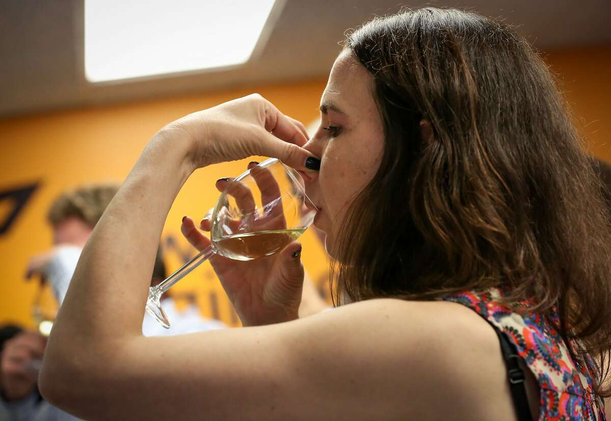 Tech industry guest, Sigal Bareket, follows instructions to plug her nose while taking a sip at the wine tasting event hosted by built.io on Wednesday, June 10, 2015 in San Francisco, Calif.