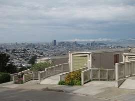 Houses in the 100 block of Topaz Way in the Diamond Heights district are modest when seen from the sidewalk, but the view from the rear is a sculptural wall of elongated wood forms -- neither of which can compete with the panoramic bay views to the east.
