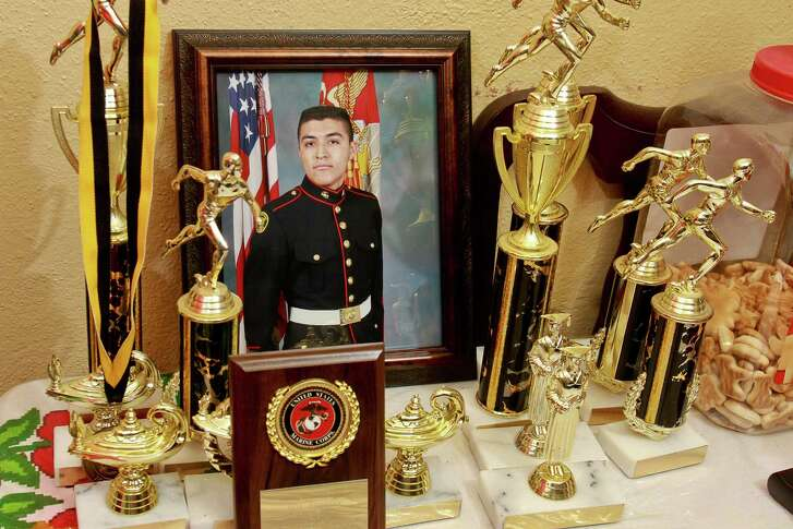 A portrait of Saul Rodriguez wearing his U.S. Marine Corps ROTC dress uniform, along side trophies and awards he earned when in USMC ROTC. Saul is a DACA (Deferred Action for Childhood Arrivals), whose personal dream is to enlist in the military. He is getting frustrated because his dream seems less possible without immigration reform since he is getting older.