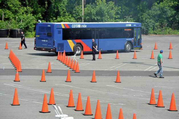 A driver backs up her bus into a spot marked with cones as Capital District Transportation Authority bus drivers compete in the CDTA Roadeo Championship on Thursday, June 11, 2015, in Albany, N.Y. Drivers were scored in ten different driving challenges, and were given a certain amount of time to finish the course.    (Paul Buckowski / Times Union) Photo: PAUL BUCKOWSKI / 00032238A