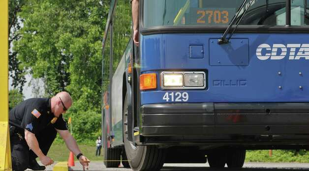 """Watervliet Police Sgt. Anthony Harbour measures the distance the bus is away from the representative curb as Capital District Transportation Authority bus drivers compete in the CDTA Roadeo Championship on Thursday, June 11, 2015, in Albany, N.Y. Drivers needed to be six inches for less from the curb for the front tires and 15"""" or less for the back tires. Drivers were scored in ten different driving challenges, and were given a certain amount of time to finish the course.    (Paul Buckowski / Times Union) Photo: PAUL BUCKOWSKI / 00032238A"""