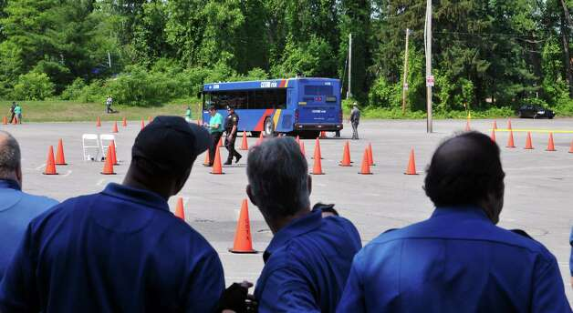 Bus drivers watch from the shade as a fellow driver goes through the course as Capital District Transportation Authority bus drivers compete in the CDTA Roadeo Championship on Thursday, June 11, 2015, in Albany, N.Y. Drivers were scored in ten different driving challenges, and were given a certain amount of time to finish the course.    (Paul Buckowski / Times Union) Photo: PAUL BUCKOWSKI / 00032238A