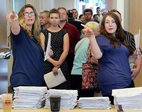 Janice Sivillo, left, and Brittany Austin, right, of The Forum Group direct job seekers during a job fair for those interested in working at Saratoga Race Course during the 2015 meet at the Saratoga Springs City Center Thursday June 11, 2015 in Saratoga Springs, NY.  (John Carl D'Annibale / Times Union) Photo: John Carl D'Annibale / 10032242A