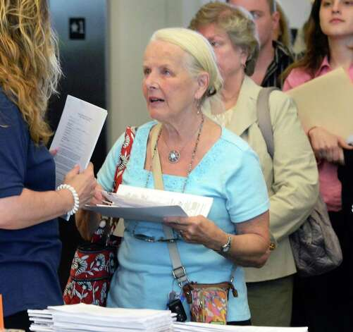 Emily Kosek, center, of Clifton Park receives an application during a job fair for those interested in working at Saratoga Race Course during the 2015 meet at the Saratoga Springs City Center Thursday June 11, 2015 in Saratoga Springs, NY.  (John Carl D'Annibale / Times Union) Photo: John Carl D'Annibale / 10032242A