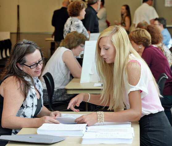 Stacey Hetherington, left, of N. Adams interviews with NYRA betting clerk Kristin Czizik during a job fair for those interested in working at Saratoga Race Course during the 2015 meet at the Saratoga Springs City Center Thursday June 11, 2015 in Saratoga Springs, NY.  (John Carl D'Annibale / Times Union) Photo: John Carl D'Annibale / 10032242A