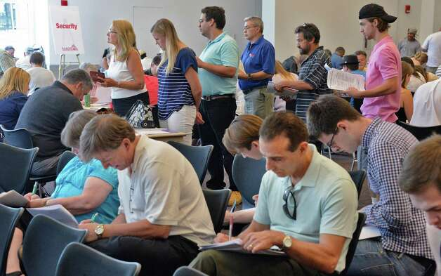 Job seekers fill out applications during a job fair for those interested in working at Saratoga Race Course during the 2015 meet at the Saratoga Springs City Center Thursday June 11, 2015 in Saratoga Springs, NY.  (John Carl D'Annibale / Times Union) Photo: John Carl D'Annibale / 10032242A
