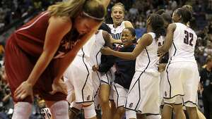 Stanford's Kayla Pedersen drops her head Tuesday night April 6, 2010 at the Alamodome in San Antonio, Texas while the UConn team celebrates their NCAA Women's Final Four Championship win over the Stanford. Connecticut won 53-47 in the first back-to-back undefeated championship seasons in the history of NCAA women's basketball. (Staff Photo by Jerry Lara/San Antonio Express-News)