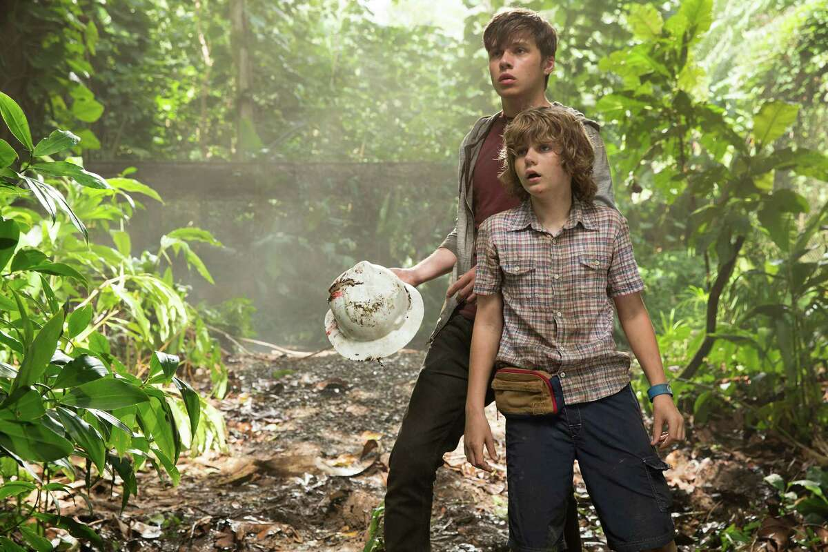 """This photo provided by Universal Pictures shows, Nick Robinson, left, and Ty Simpkins in a scene from the film, """"Jurassic World,"""" directed by Colin Trevorrow, in the next installment of Steven Spielberg's groundbreaking """"Jurassic Park"""" series. The 3D movie releases in theaters by Universal Pictures on June 12, 2015. (Chuck Zlotnick/Universal Pictures via AP) ORG XMIT: CAET776"""
