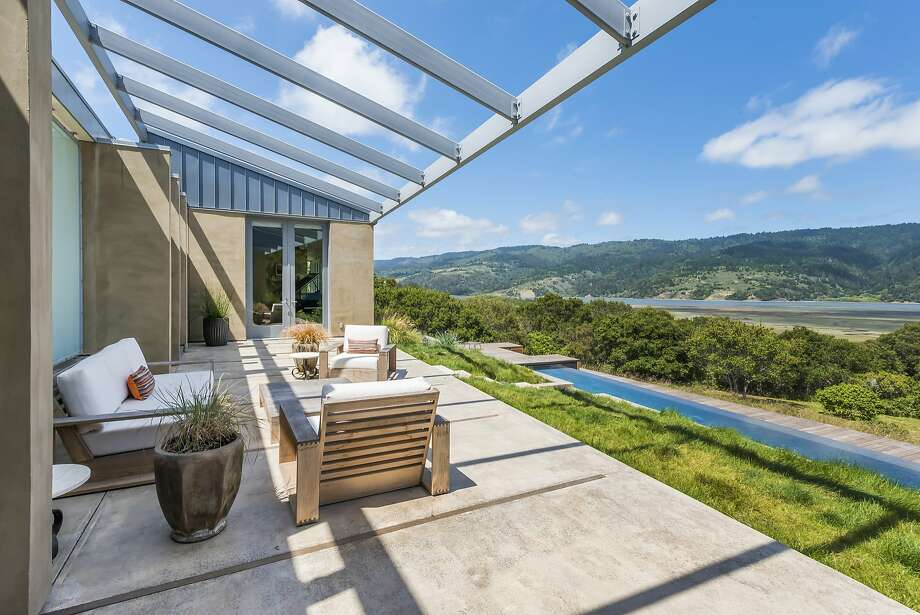 Multiple rooms access the concrete patio overlooking Bolinas Lagoon.